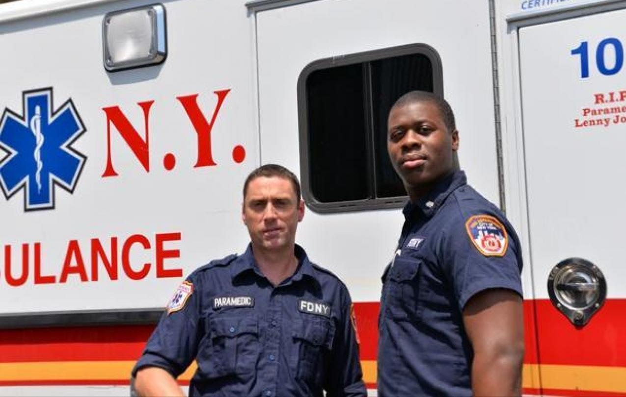 EMT Niall O'Shaughnessy, left, and his partner Moses Nelson stand by their emergency vehicle.