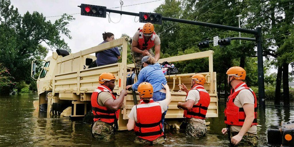 National Guard helping a woman into a truck during the Hurricane Harvey evacuation